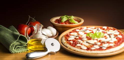 Pizza with ingredients on the wooden table