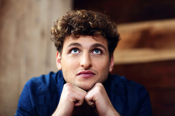 Portrait of a pensive man with curly hair looking up