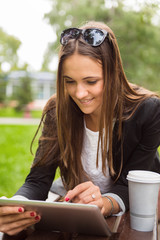 Young brunette woman using digital tablet outdoor in a park. Sum
