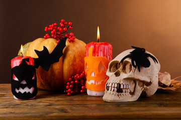 Composition of decorative skull, pumpkin, candles and Halloween