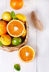 Oranges, lemons and limes over white wooden background
