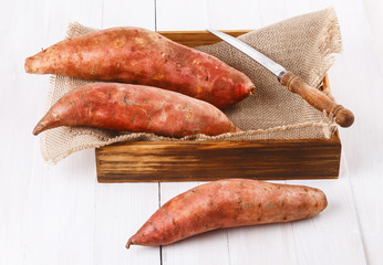 Sweet potato over white wooden background