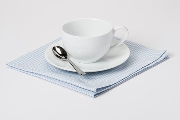 Cup, Plate And Spoon On Folded Gingham Cotton Napkin. White Back