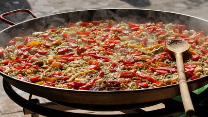 cooking Spanish paella with wooden spoon