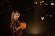 woman with pumpkin in dark forest