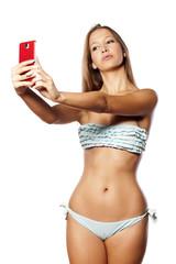 beautiful young girl in bikini takes a selfie