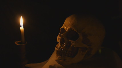 Halloween image with human skull and burning candle