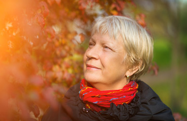 Portrait of a beautiful middle-aged woman outdoors. Sunlight.