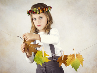 Beautiful little girl with autumn leaves