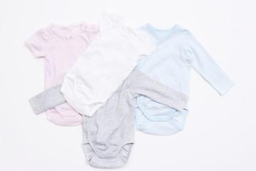Assorted babygros against white background