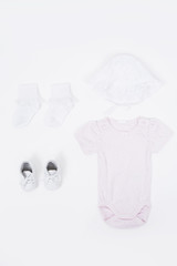Babygro, socks and booties against white background