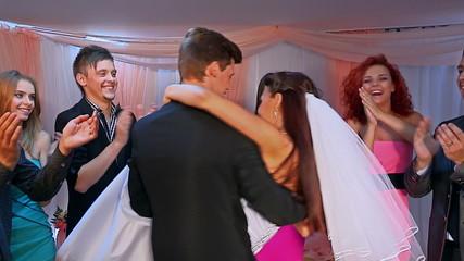 Newlyweds spinning at wedding dance.