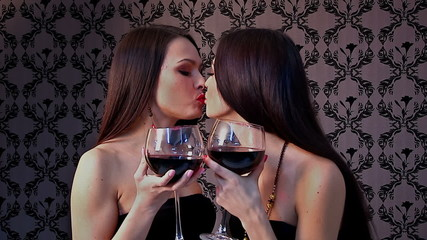 Couple  kissing lesbian women kissing and drinking wine. .