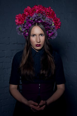 Beautiful femme fatale in a headdress from fresh colorful flower