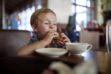 Little boy having sandwich in a cafe