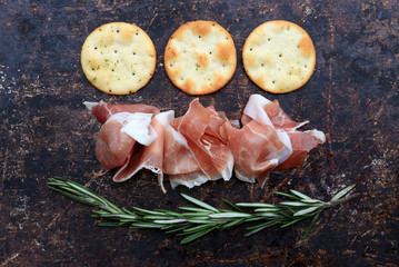 Prosciutto, rosemary and crackers on brown rustic background