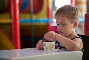 Little child eating chocolate ice cream