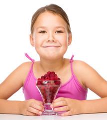 Happy little girl is eating raspberries