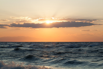 Rough sea and sunsetr over it