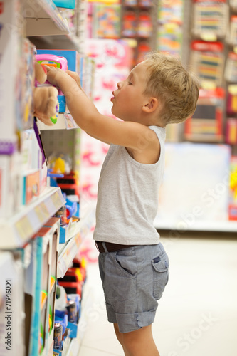 Boy choosing toy in the shop - 71946004