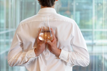 fit flexible  business man with flask of water in lab