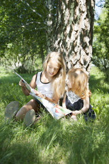 sisters reading the book on picnic