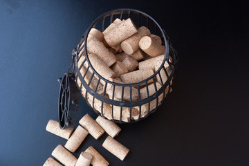 Cork cage filled with blank wine corks stays on black surface