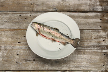 Fresh fish on white plate and vintage wooden table