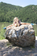 girl lying on a rock and enjoying river  view
