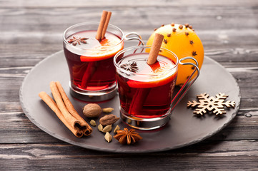 Christmas mulled wine with spices on wooden background