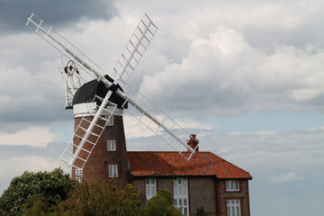 A Traditional Windmill Adjacent to a Brick House.