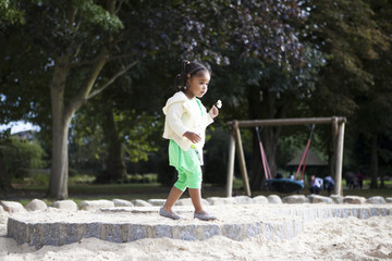 Small child on playground with flower