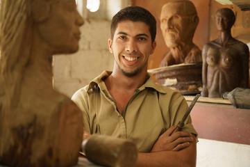 Portrait man working happy artist art wood sculpture in atelier