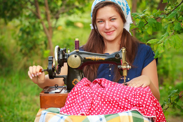 Young woman with retro hand sewing machine