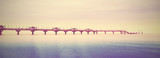 Retro filtered picture of long pier into the sea.