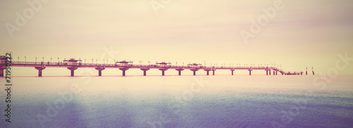 Retro filtered picture of long pier into the sea. - 71950222