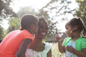 Family with dark skin playing with soap bubbles