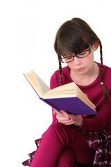 Little girl wearing glasses reading a book on white background.