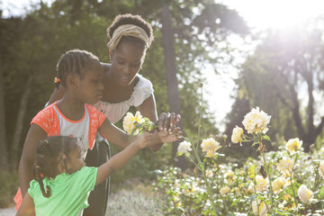 Family of African descent in park smelling flowers