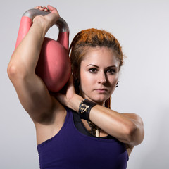 Portrait close up of young attractive female doing kettle bell e