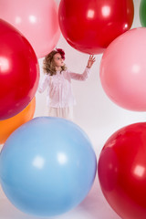 Beautiful girl in a white blouse is considering large balloons.