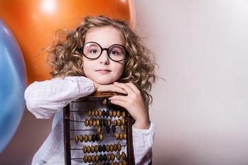 Girl schoolgirl with wooden abacus.