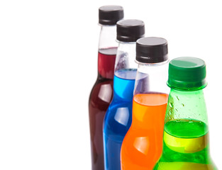 Multicolored soda drinks in bottles over white background