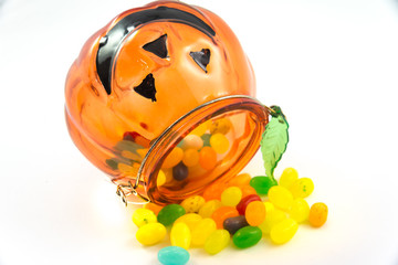 Jelly beans drop from pumpkin glass isolated