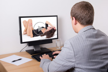 business man watching erotic video on his personal computer