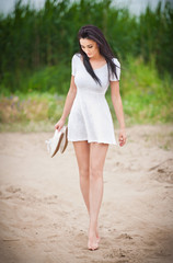 Attractive brunette girl with short white dress walking