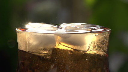 Stream of Champagne in a Glass with Ice