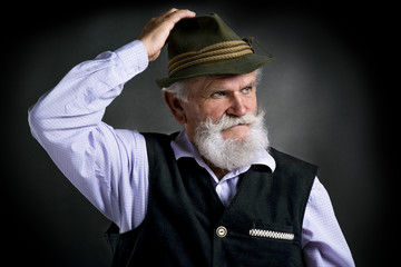 Old bavarian man in hat on black background