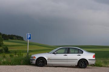 Silver car parking on a green field