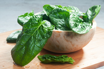 Fresh spinach in a wooden bowl on a cutting board